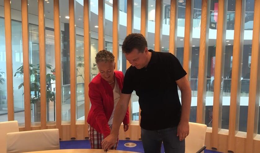 Wethouder Van Tatenhove en Leon Vijverberg snijden de taart aan.