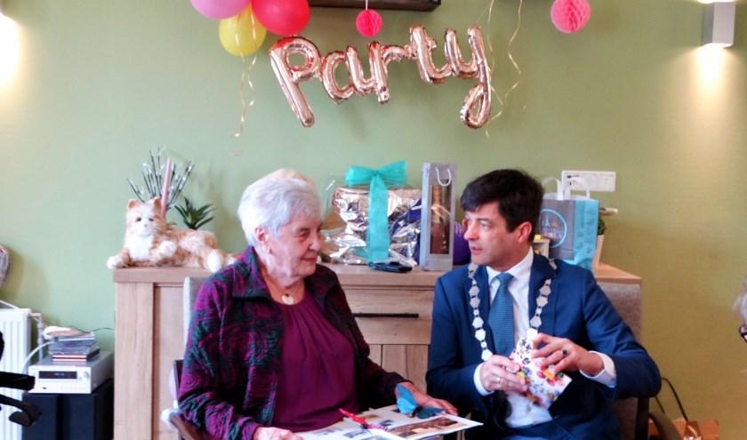 Neeltje van Gemeren-Kruithof pakt samen met de burgemeester haar cadeautjes uit.