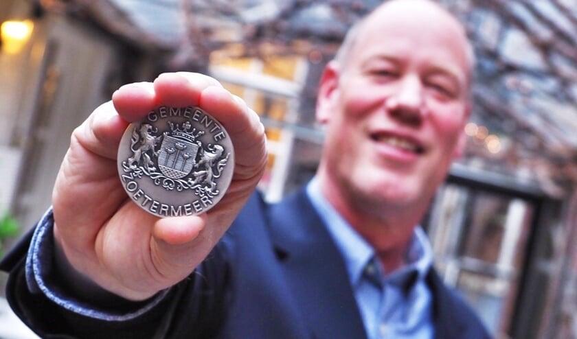 Marco Sikkel toont trots de Zoetermeerse gemeentepenning.