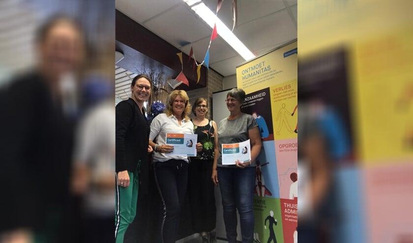 De twee nieuwe vrijwilligers ontvangen een certificaat.