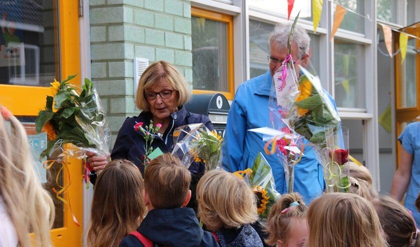 Het schoolplein stond vol kinderen met bloemen.