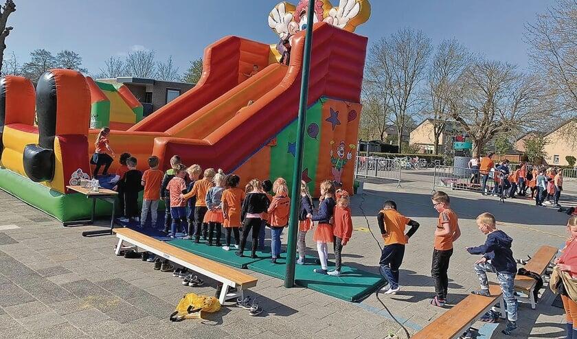 <p>Kinderen staan in de rij voor de grote glij-springkussen bij de Howiblo.</p>