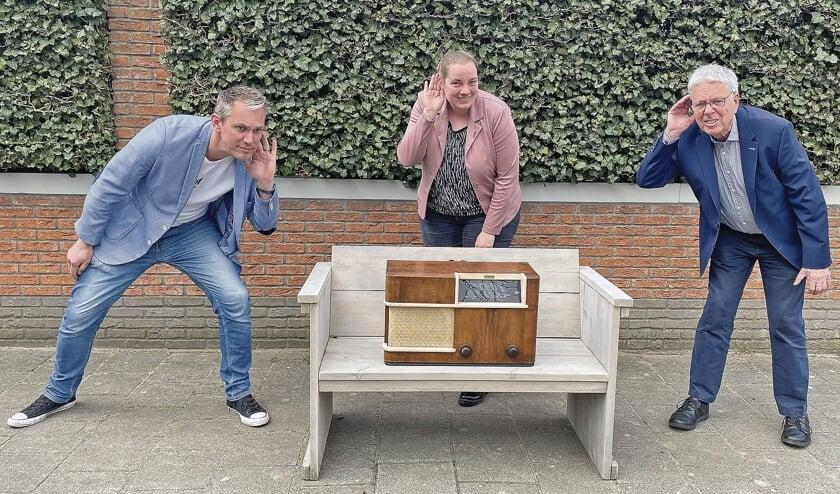 """<p pstyle=""""BODY"""">Mark te Poele, Nynke Vergeer en Kees Bazuine met de oude radio uit oorlogstijd, een van de gebruikte voorwerpen die terugkomen in de speurtocht.</p>"""