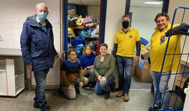<p>de vrijwilligers van de Speelgoedbank en de Lions, met achter hen de voorraad speelgoed</p>