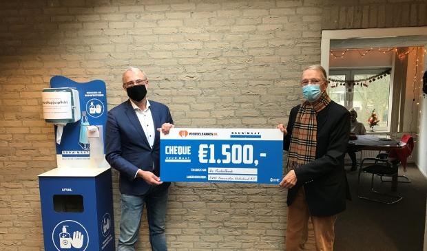 overhandiging cheque 1500 euro aan de Voedselbank. links Pieter van Leusden en rechts Jan Dijkstra
