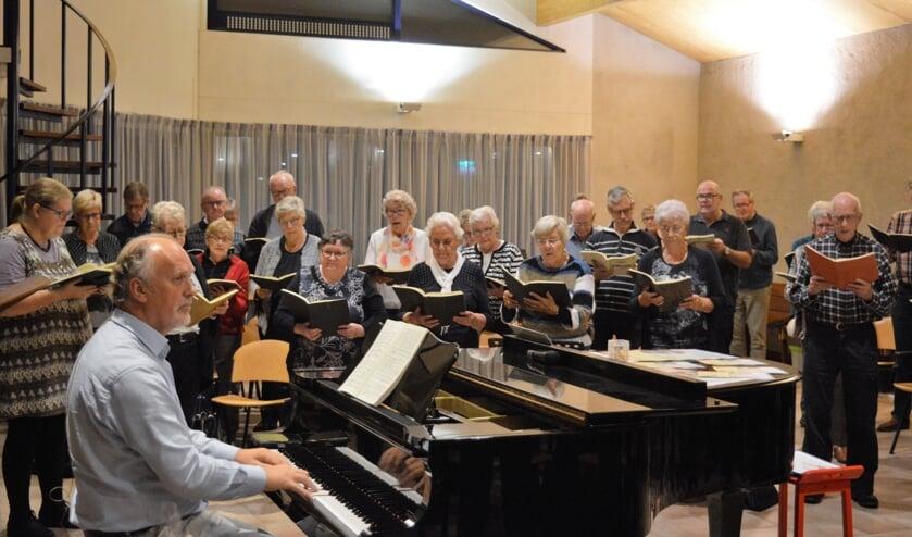 Dirigent Hans Cok achter de piano bij een koorrepetitie