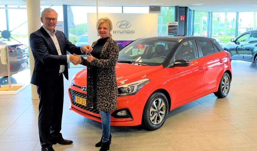 Arie Hartog overhandigt de sleutels van de Hyundai i20 aan Loes de Raaij.