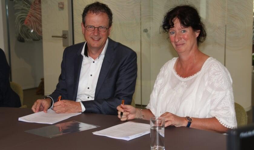 Alfred van den Bosch (Wooncompas) en Sonja Krau (IJsselmonde-Oost) ondertekenen het huurcontract