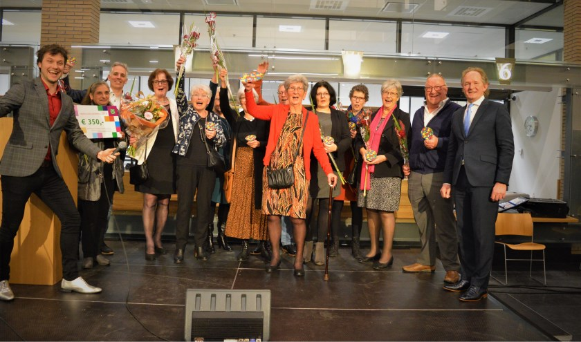 Nel van Ballegooijen (midden) op het podium met vrijwilligers van de Voedselbank. Wethouder Japenga (rechts) reikte de prijzen uit