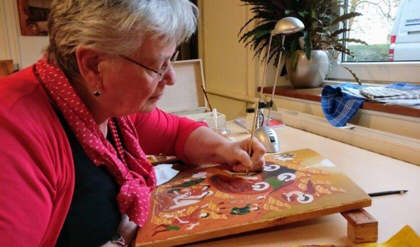 Mieke Mudde bij het schilderen van een icoon