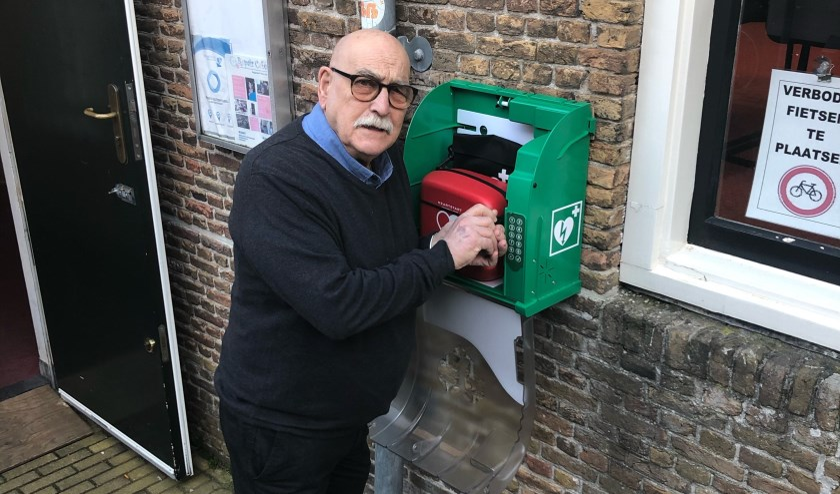 Wijkcentrum beheerder Aad Blaas bij de AED in De Boekenstal.