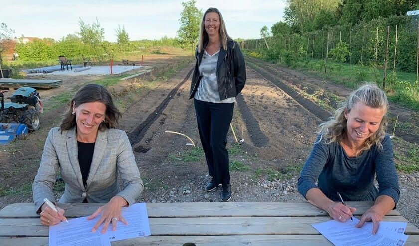 Ingrid Hartog (links) en Claudia Reijnen tekenen de samenwerkingsovereenkomst. Linda Sanders kijkt toe.