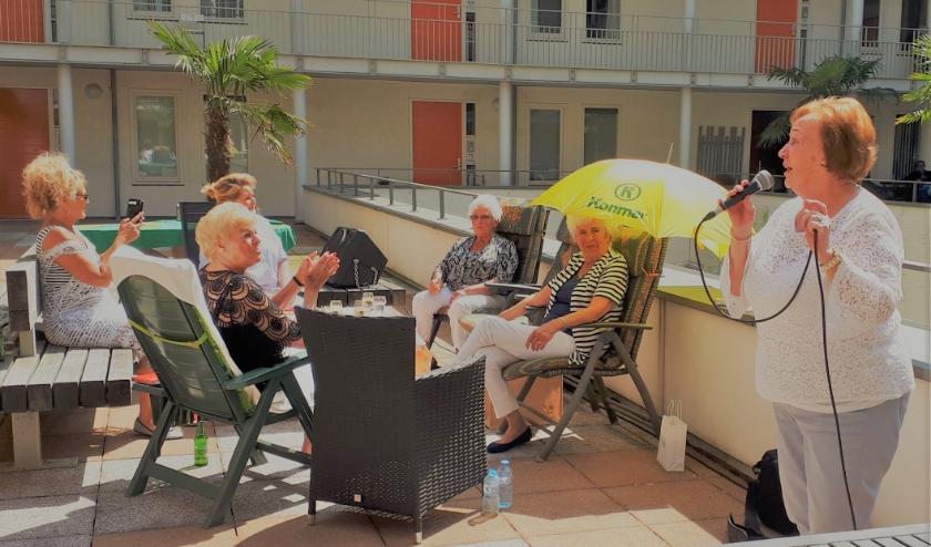 Op de foto is Annie aan het zingen, mevrouw Kurvers onder de gele parasol werd 81 jaar die dag. De stemming zat er goed in tijdens de Balkonbingo...