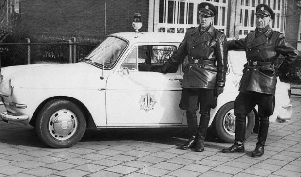 <p>De hoofdagenten Sollie en Punt bij hun surveillanceauto</p>