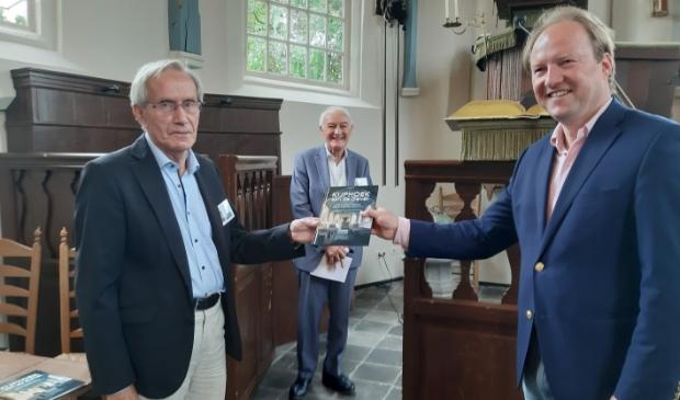 <p>Auteur Kees Brinkman (links) overhandigt het eerste exemplaar aan burgemeester Hein van der Loo. </p>