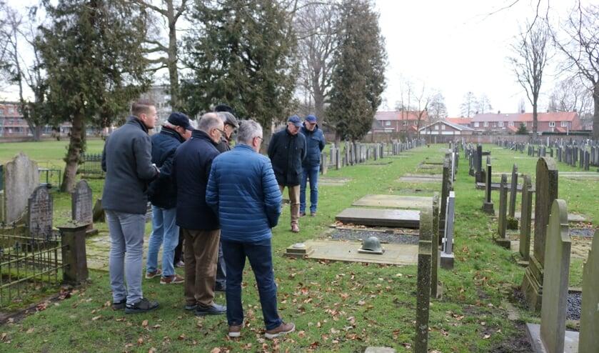 Rijssen - De stadsgidsen van het Rijssens Museum krijgen instructie van oud-begraafplaatsbeheerder Johan Nijzink op de Oude Begraafplaats bij een oorlogsgraf.