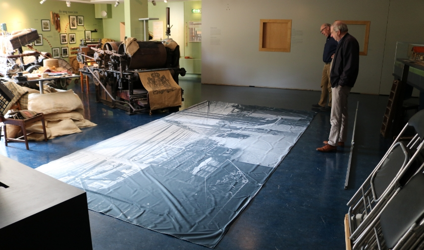 RIJSSEN - Jan van de Maat en Johan Nijzink bekijken de levensgrote wandfoto voor de jutekelder.
