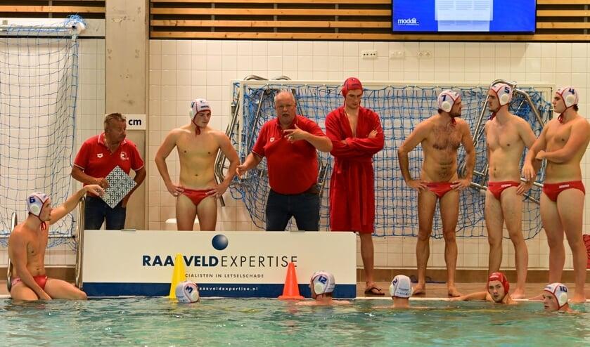 <p>De heren van Het Ravijn worden door Zeno Reuten tijdens de wedstrijd in Amersfoort tegen ZPC Amersfoort toegesproken. (foto: Wim Beunk)</p>