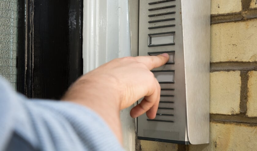 Close up view of the hand of a man ringing an intercom to gain access to an apartment building or business premises, wall-mounted on brickwork