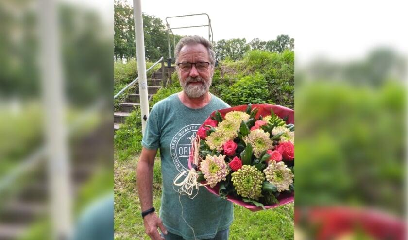 <p>Mannes Pijffers ontvangt een grote bos bloemen, omdat zijn jonge duif als eerste terugkeert op het hok vanuit Beek en Donk</p>