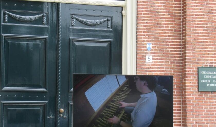 <p>Beiaard en organist Jan-Geert Heuvelman was goed in beeld op het grote scherm bij de ingang van de kerk</p>