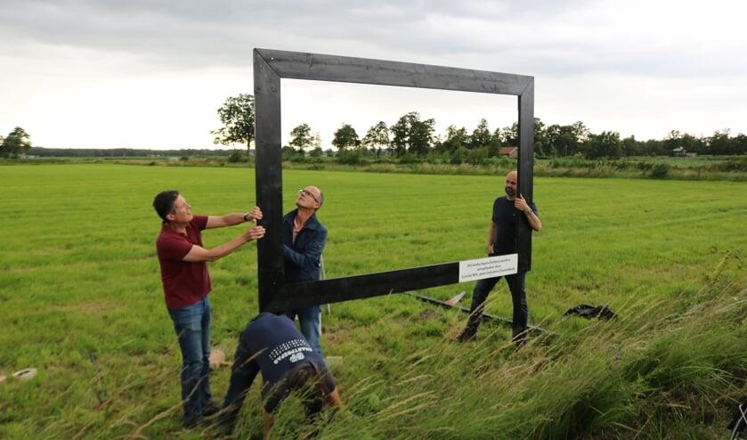 <p>Leden van het actiecomit&eacute; geen industrie in Elsenerbeek plaatsen het landschapsschilderij. Binnen de lijst links Gert-Jan Geerling (links) en Leo Nieuwenhuis. &nbsp;</p>