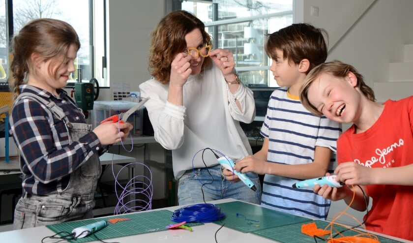 <p>Pleun Burks, Wencke Steggink (Tetem), Nilson Boensma en Gijs Steggin, bezig met het maken van een bril m.b.v. een 3D-pen. Foto: Linda Meijer</p>
