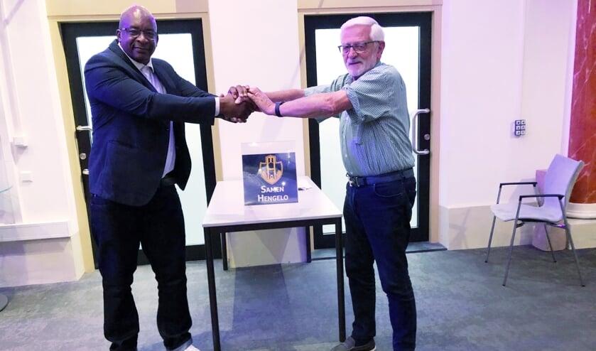 <p>Buddy Peter Blankeslijn reikt asielzoeker Herme letterlijk en figuurlijk de hand, net als hun nieuwe logo! (Foto: PR)</p>