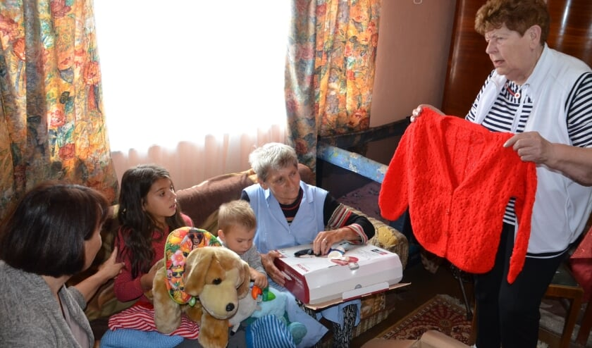 <p>Riky Schonenborg deelt kleding uit aan arme Roemenen. Foto: Raymond Wegdam.&nbsp;</p>