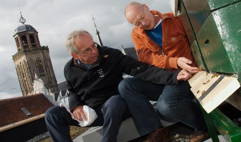 Frans Kapsenberg (links) en Frank Leenen bij de bijenkasten op het dak van het Deventer stadhuis. (foto Gert Perdon)