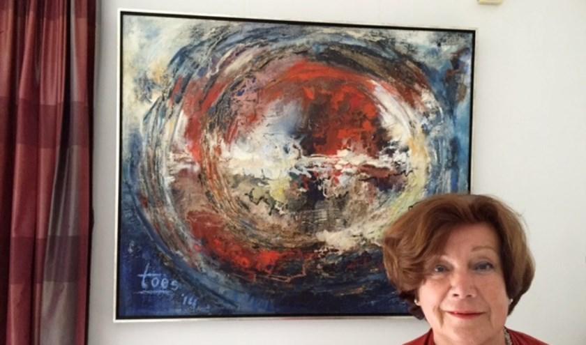 Toos Boekhoven thuis voor haar schilderij 'Wereld in verwarring.'