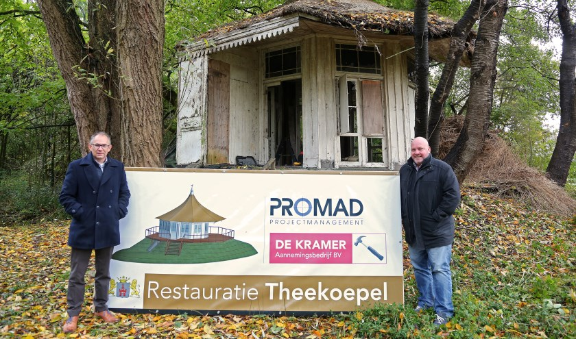 Wethouder Bert Vermeij (l) en Rob Stekelenburg (Promad) markeren de restauratie van de theekoepel aan de Papenhoef bij het onthulde bouwbord. Foto: Alex de Kuijper