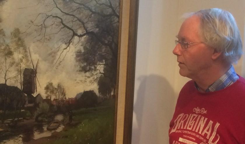 Museumvrijwilliger Ron Maat bij het schilderij van Jan van Vuuren, waarop  molen De Fortuin fier omhoog torent.