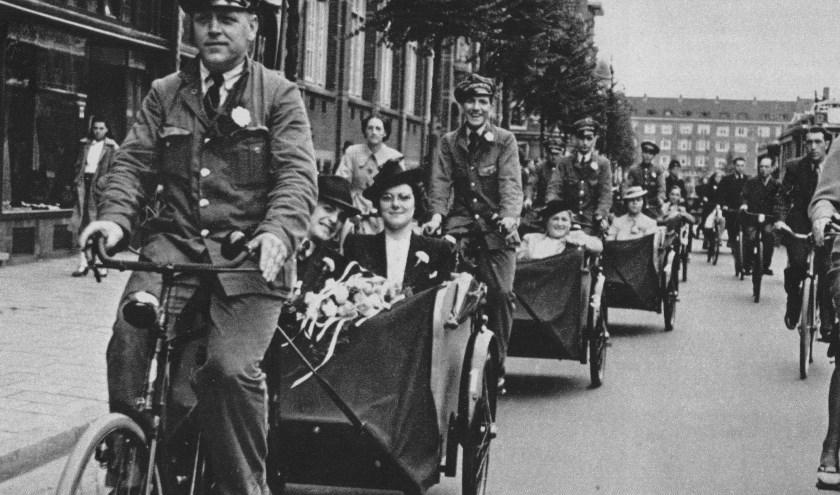 Een trouwerij in 1942. Taxichauffeurs vervoeren het bruidspaar per fiets, omdat de bezetter alle benzine in beslag heeft genomen.