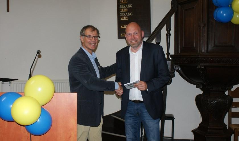 Marcel de Reuver overhandigt het eerste exemplaar van zijn gedichtenbundel aan wethouder Hans Kokke. Het boekje is een cadeau van de gidsen aan hun deelnemers. foto: Jan Loonen