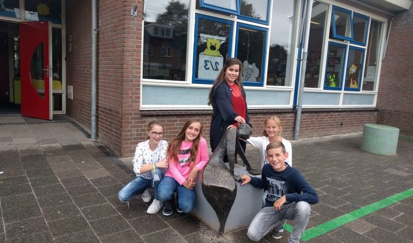 Sanne Telgenkamp met vier scholieren bij het Beeld van de Maand: Schrijvend Meisje