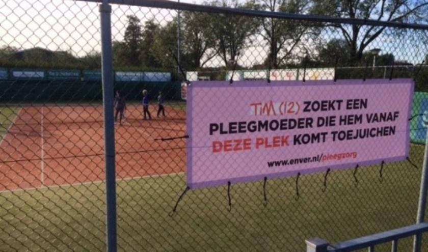 Toelichting op afbeelding: pleegzorg spandoek voorbeeld bij Tennisvereniging Smitshoek in Barendrecht. Opschrift op spandoek is: Tim (12) zoekt een pleegmoeder die hem vanaf deze plek komt toejuichen.