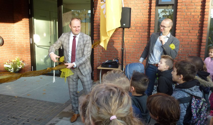 Wethouder Dennis Gudden knipt het lint door. Daarmee is de school geopend.
