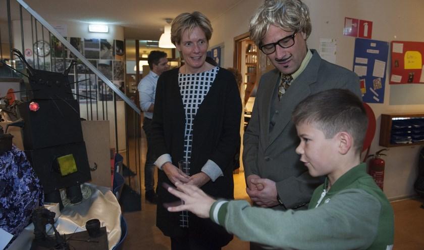 Een leerling van basisschool De Regenboog in Bemmel legt wethouder Helga Witjes uit hoe de kunst tot stand is gekomen. (Ellen Koelewijn)
