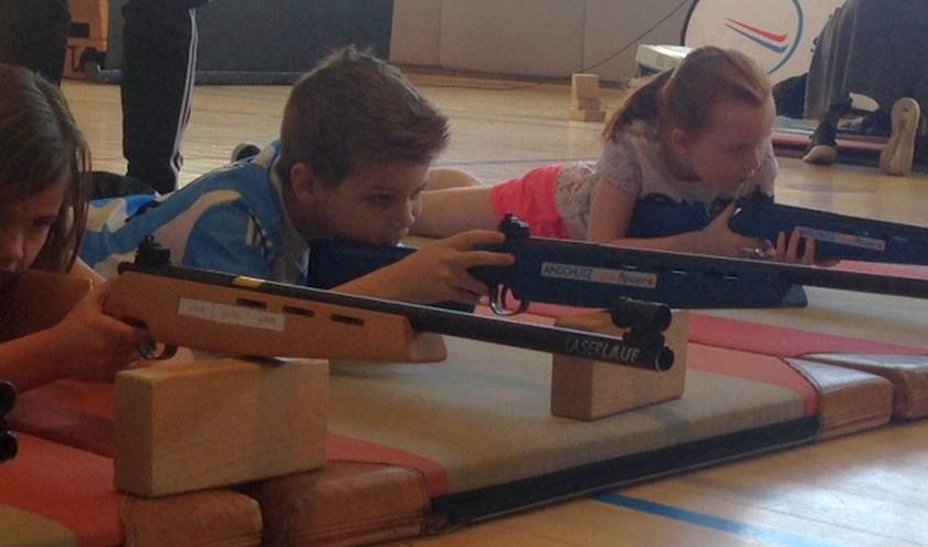 De kinderen schoten met geweren, die gebruikt worden bij de biatlon.