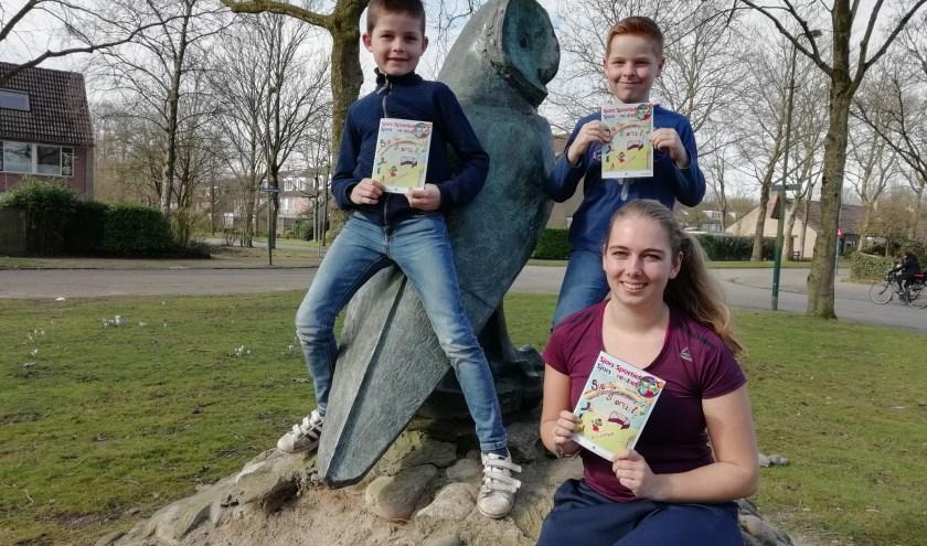 """Bram (links), Senne en vakleerkracht gymnastiek Michelle van Basisschool Uilenburcht met het boekje Sjors Sportief en Creatief. """"Lasergamen lijkt ons wel leuk,"""" zeggen Bram en Senne."""