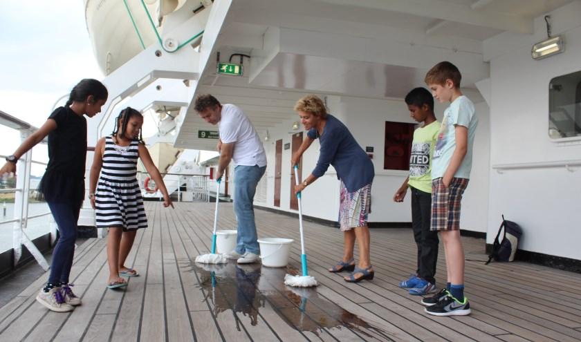 Onder toeziend oog van een aantal kinderen moesten de twee directeuren van KindeRdam en Eisvrij het dek van het historische cruiseschip schrobben.