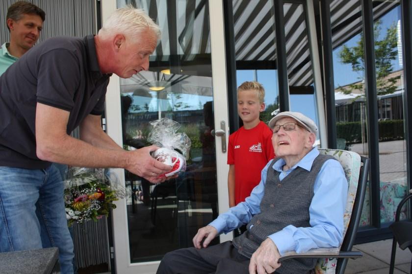 Vosseveld voorzitter Harry Bakker spreekt Jan bonnink toe en overhandigd hem een geschenk. Achterkleinzoon Tycho (8) kijkt toe