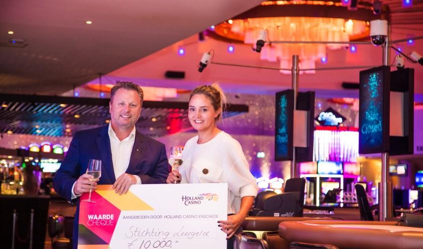 Casinodirecteur Hans van der Veen overhandigt de cheque aan de coördinator van de Stichting Leergeld Enschede Daniëlle Poortier. Foto: Reza Jalilpour