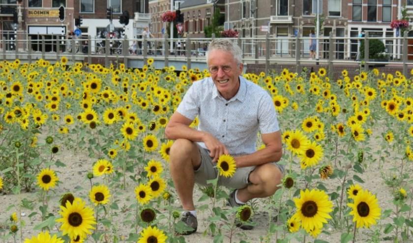 Delftenaar Simon Huiberts tussen 'zijn' zonnebloemen bij het station. (foto: indebuurt/delft).