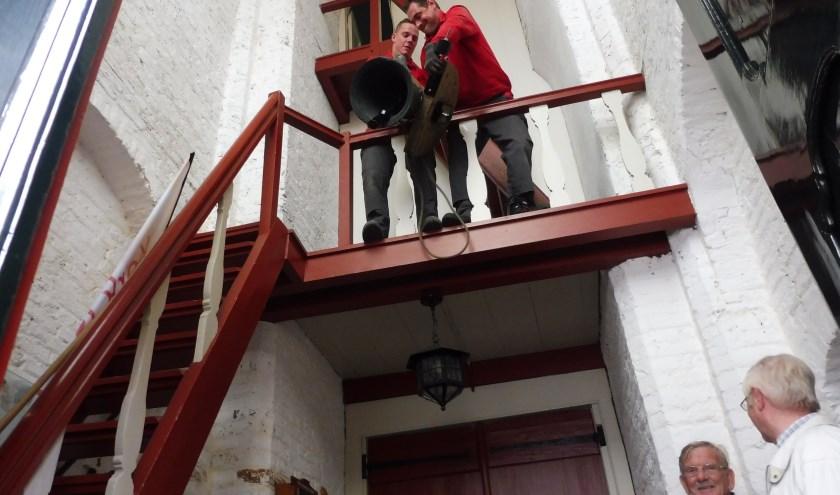 Het zorgvuldig inhangen van het 40 kilo zware klokje. Met onder links klokkenluider Piet Hogendoorn. Naast hem Pim van 't Woud, secretaris van Vereniging Oud-Linschoten. (Foto: Janneke Severs-Hilgeman)
