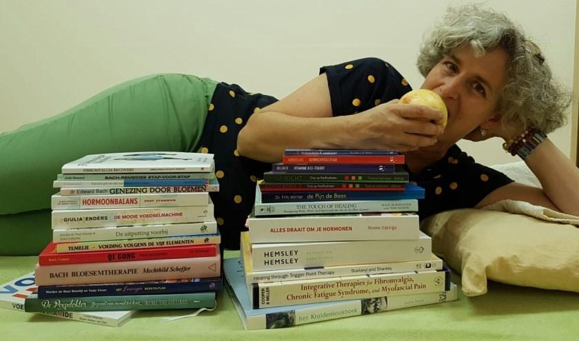 Patricia van Amerom liggend achter stapel boeken