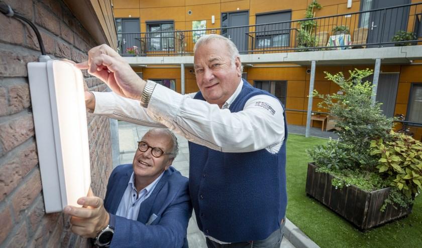 André Aansorgh, voorzitter huurdersvereniging Ookbions (rechts), en Harry Rupert, directeur-bestuurder Welbions bevestigen de eerste ledlamp. Foto: Rikkert Harink
