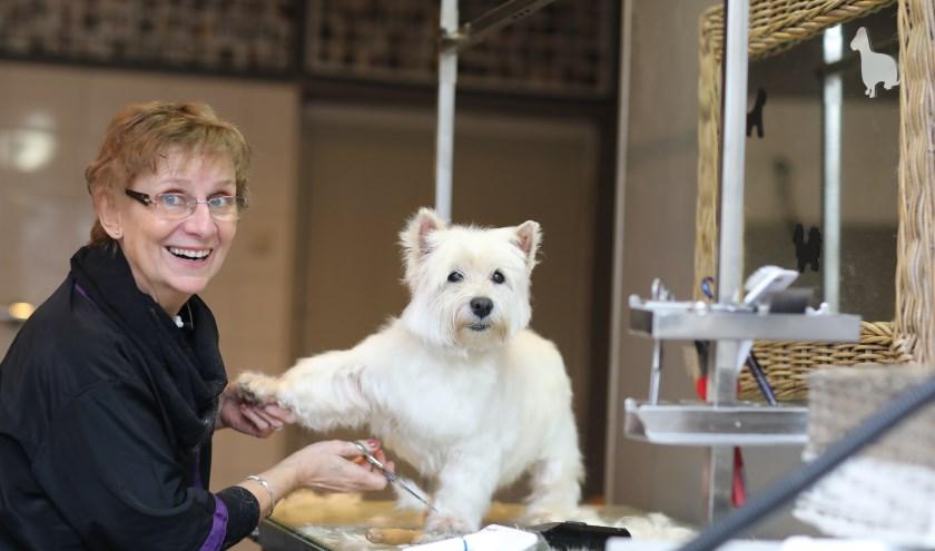 """Jeannine met Joy in de trimsalon. """"Behalve voor wassen en knippen kun je hier ook terecht voor het knippen van nagels of een hondenmassage."""" (foto: Feikje Breimer)"""