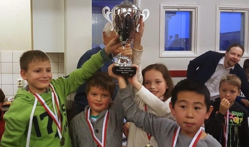 Trots wordt de beker omhoog gehouden door het team van Calluna.  Van links naar rechts: Alexander Ivanov, Yarik Shirokov (topscorer), Magi Shirokov en Kelvin Ma. (foto: Rinus van der Molen)
